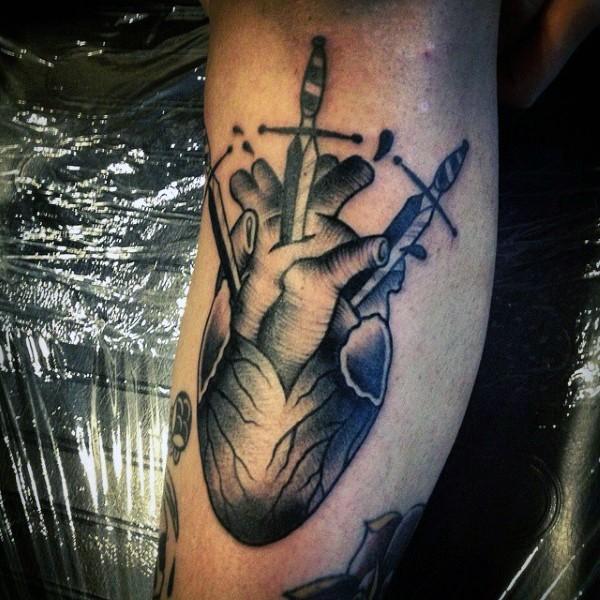 Big black ink bleeding heart with swords tattoo on leg