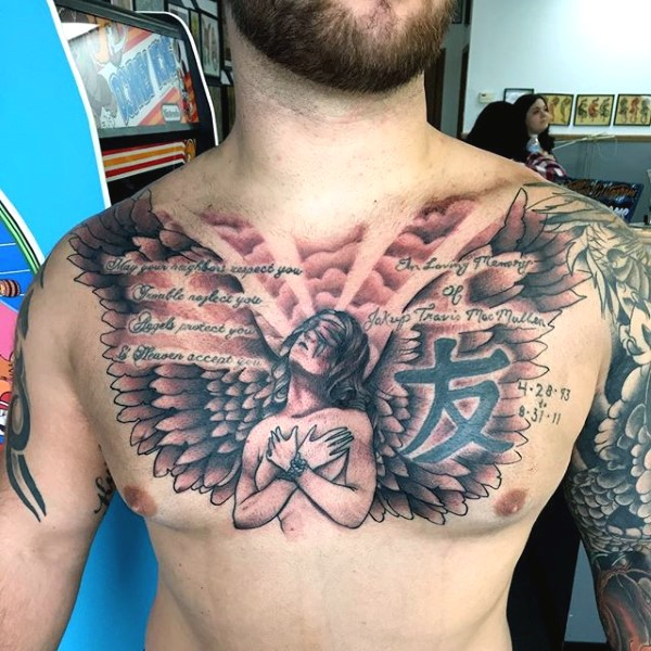 Big black ink Christian tattoo with angel and lettering on chest
