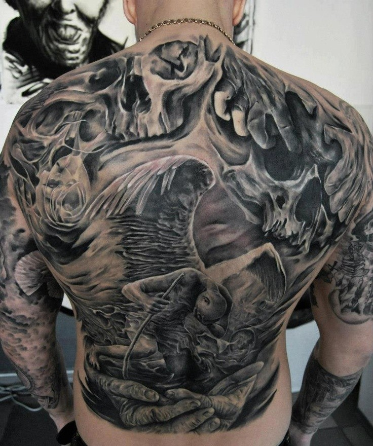 Big black ink detailed fallen angel tattoo on whole back combined with skulls