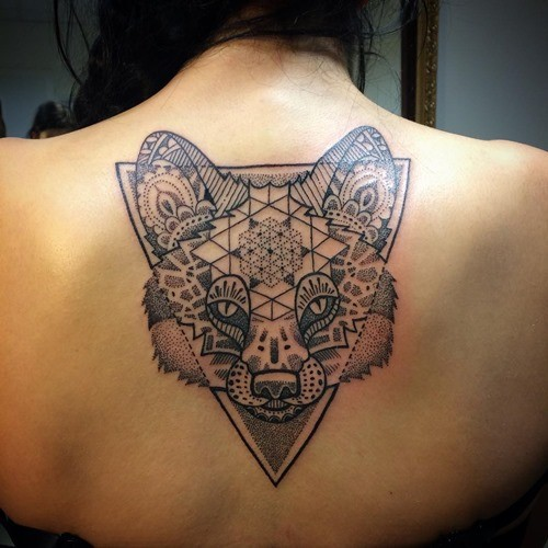 Big black ink fox head tattoo on upper back stylized with various tribal ornaments