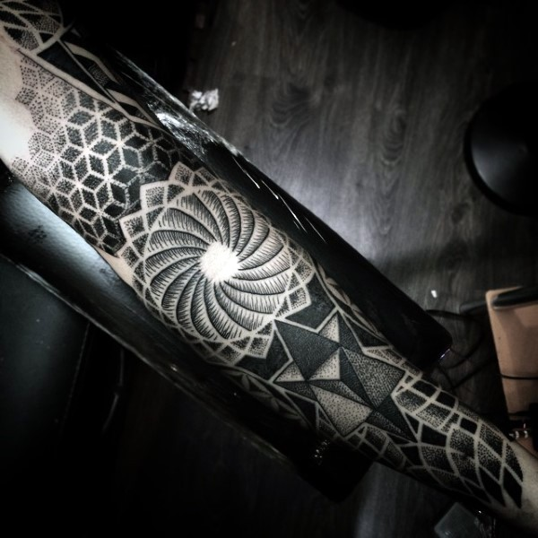 Big black ink mystical designed hypnotic symbol on sleeve combined with various geometrical ornaments
