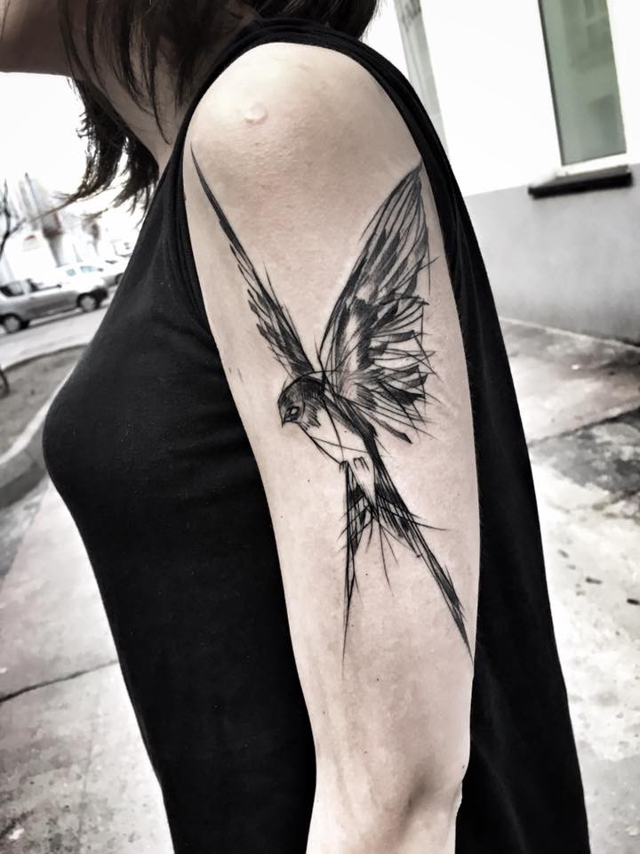 Big black ink sketch style painted by Inez Janiak upper arm tattoo of flying bird