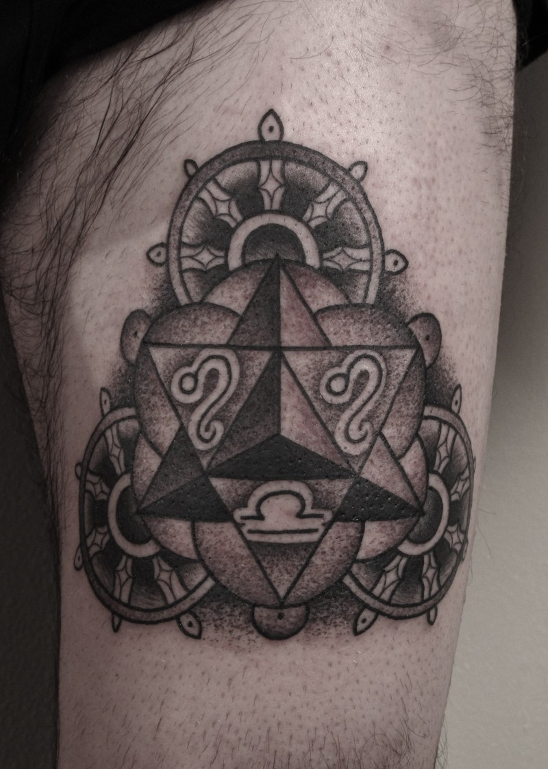 Big black ink thigh tattoo of steering wheels with zodiac symbols