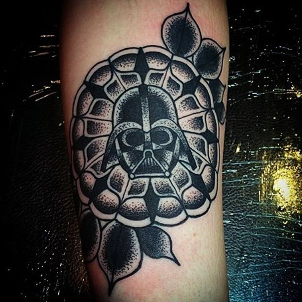 Big black ink tribal style flower tattoo on forearm stylized with little Vaders mask
