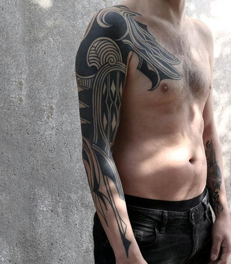 Big black ink tribal style ornaments tattoo on sleeve and chest