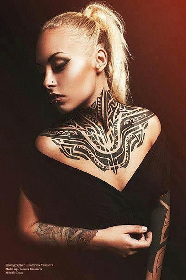 Big black ink tribal style ornaments tattoo on neck and chest