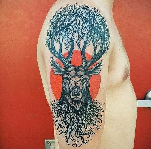 Big black ink upper arm tattoo of deer with trees