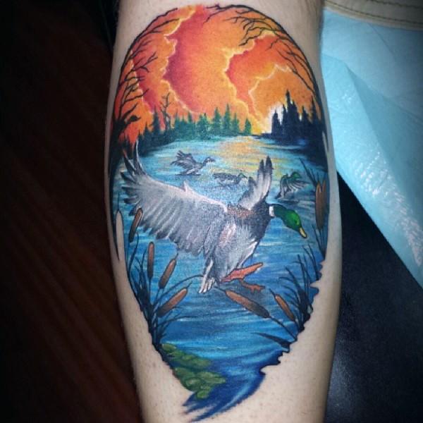 Big cartoon style colored leg tattoo of ducks at lake