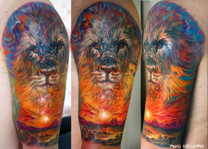 Big colored lion head tattoo on shoulder combined with desert sunrise