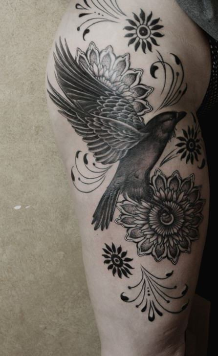 Big colored natural looking bird tattoo on thigh combined with various flowers