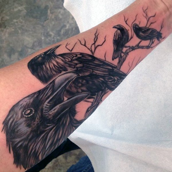 Big colored realistic looking crows with tree tattoo on sleeve