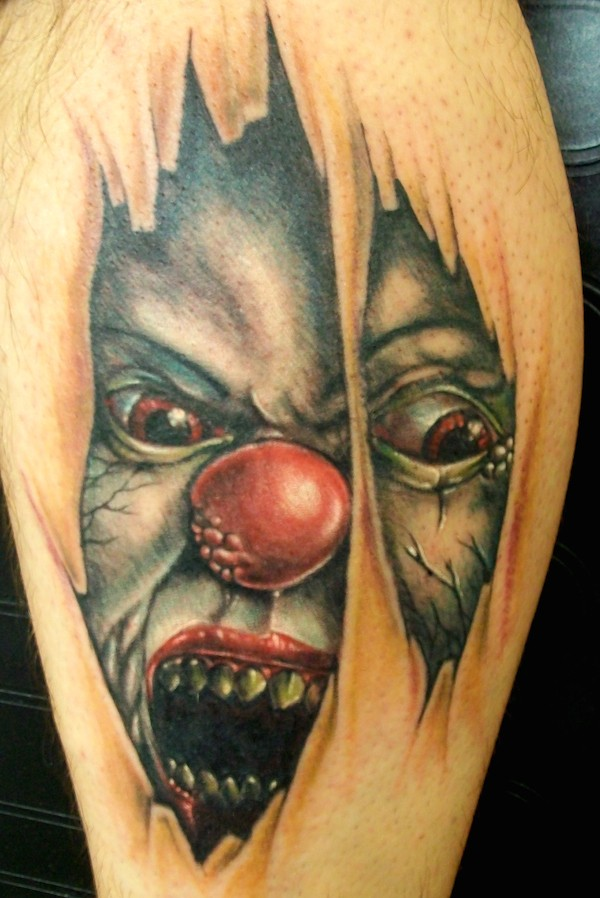 Big colored terrifying leg tattoo of under skin monster clown