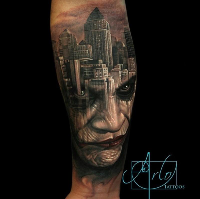 Big forearm tattoo of night city sights and Joker portrait