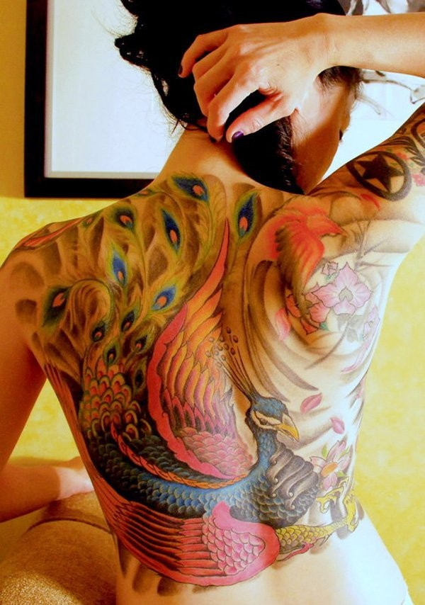 Big illustrative style colorful peacock tattoo on back combined with phoenix and flowers