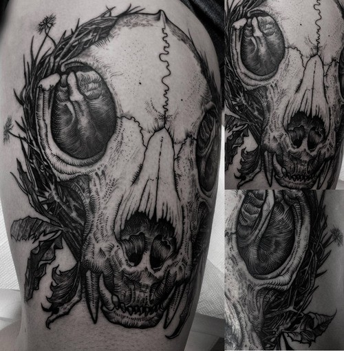 Big interesting looking thigh tattoo of animal skull with flowers