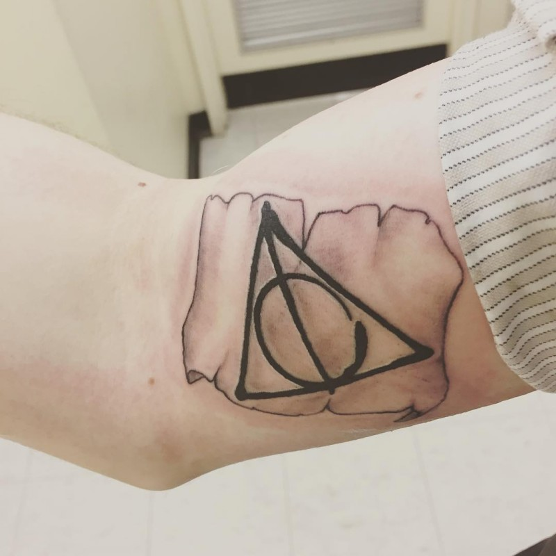 Big interesting painted colored biceps tattoo of geometric figure and antic paper