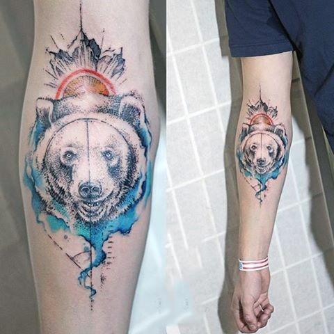 Big multicolored bear head with sun tattoo on arm