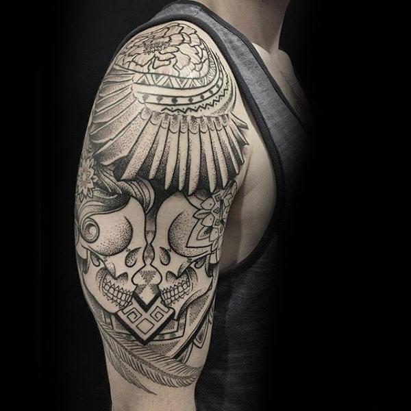 Big mystical designed upper arm tattoo fo human skulls with flowers