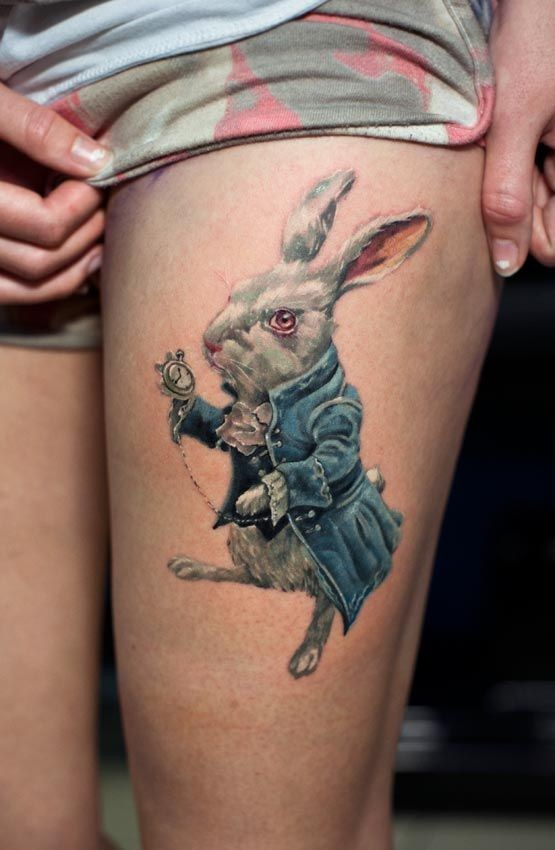 Big natural looking detailed rabbit with old clock tattoo on thigh zone