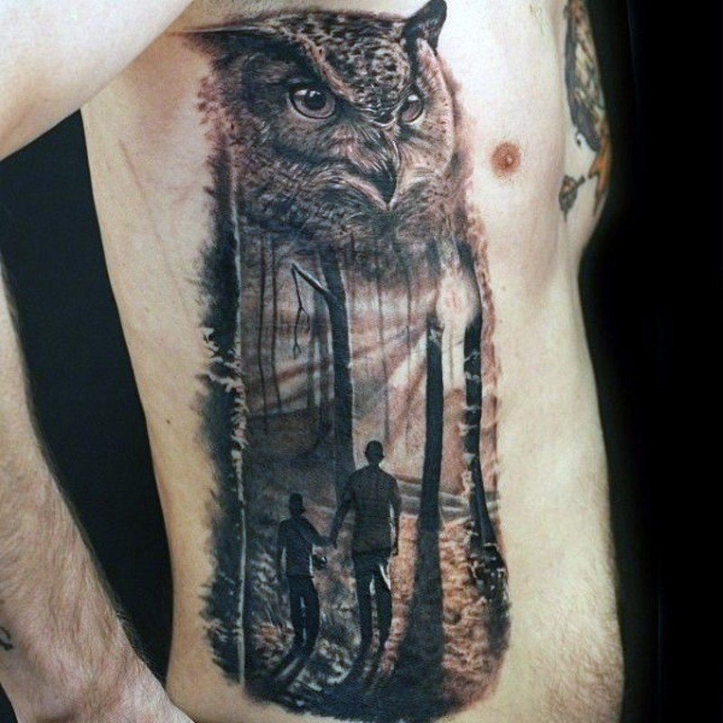Big realistic looking colored owl stylized with father and son in forest tattoo on side