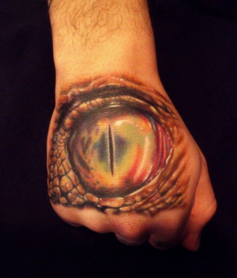 Big realistic looking dragon eye tattoo on hand