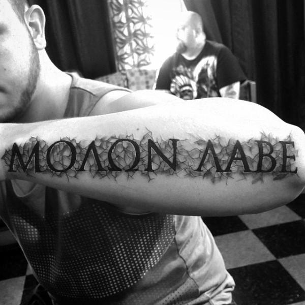 Big simple black ink Latin lettering tattoo on arm