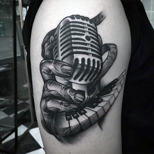 Big vintage style painted black ink microphone with piano keys tattoo on shoulder