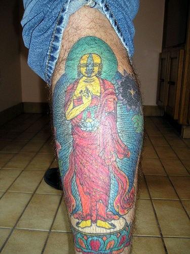 Big yellow buddha tattoo on leg