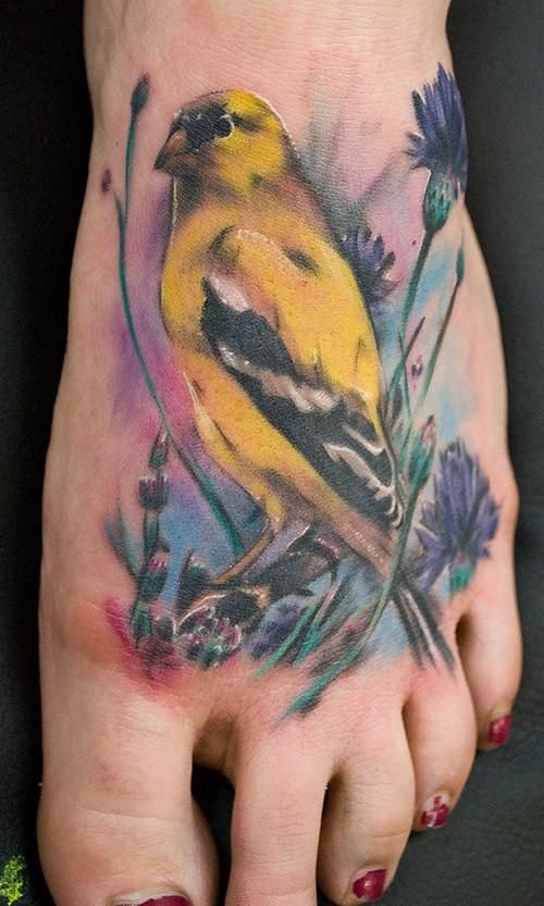 Tatuaggio colorato sul piede l&quotuccello giallo & i fiori