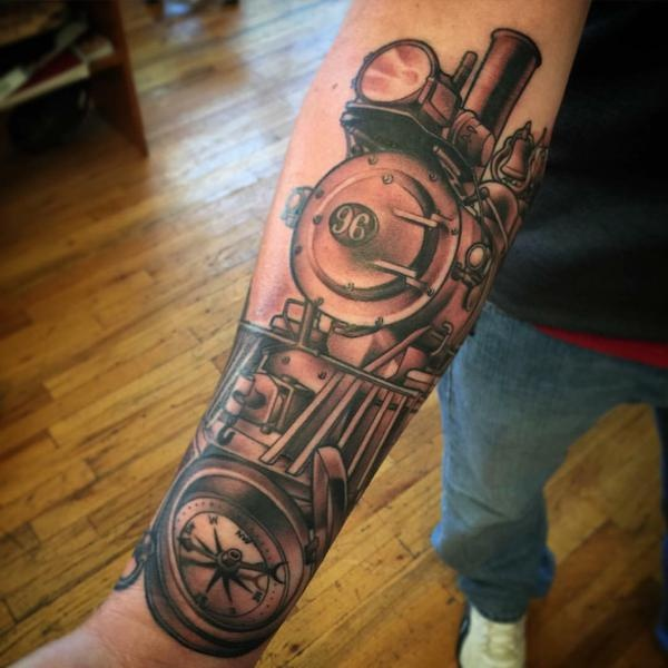 Black and gray style amazing looking train with compass tattoo on forearm