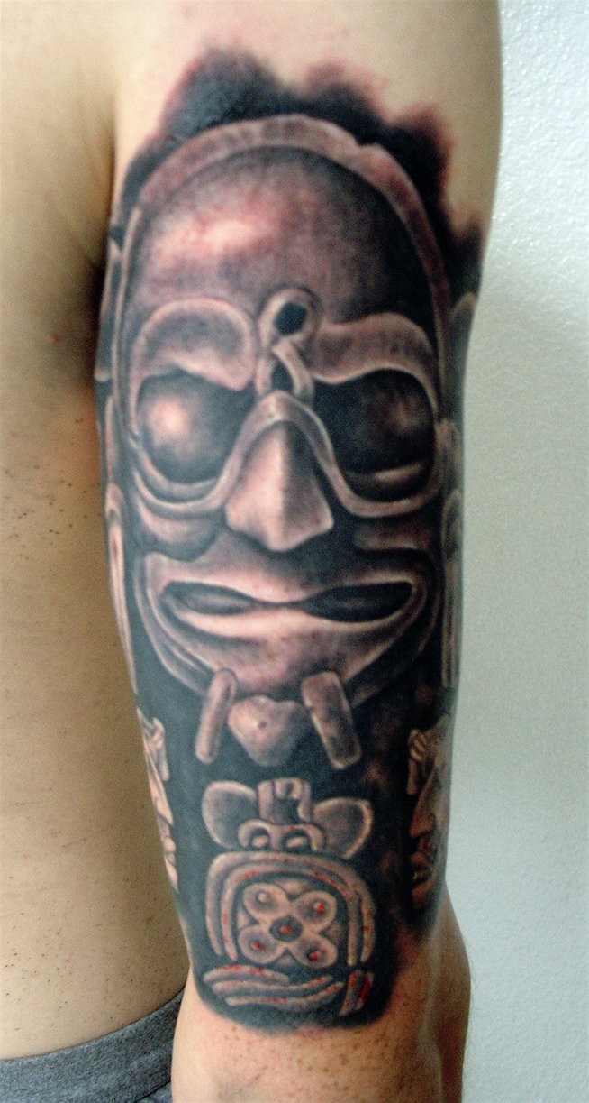 Black and gray style arm tattoo of stone statue