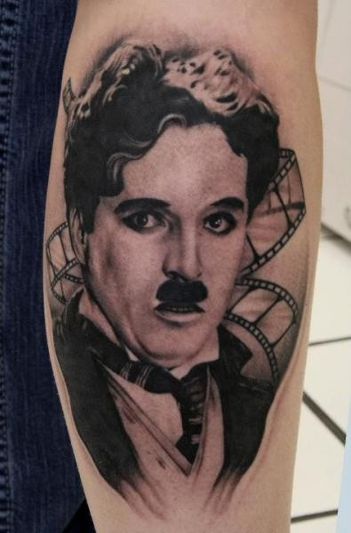 Black and gray style arm tattoo of Charlie Chaplin