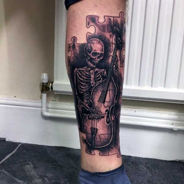 Black and gray style awesome looking puzzle tattoo on leg stylized with playing skeleton