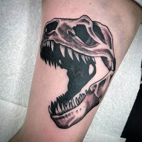 Black and gray style biceps tattoo of dinosaur skeleton