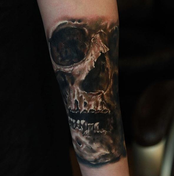 Black and gray style colored arm tattoo of human skull