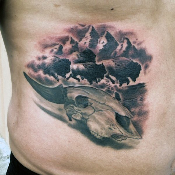 Black and gray style colored back tattoo of animal skull with bulls