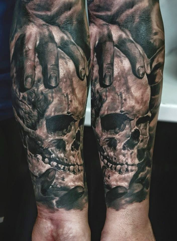 Black and gray style colored forearm tattoo of human hand holding skull