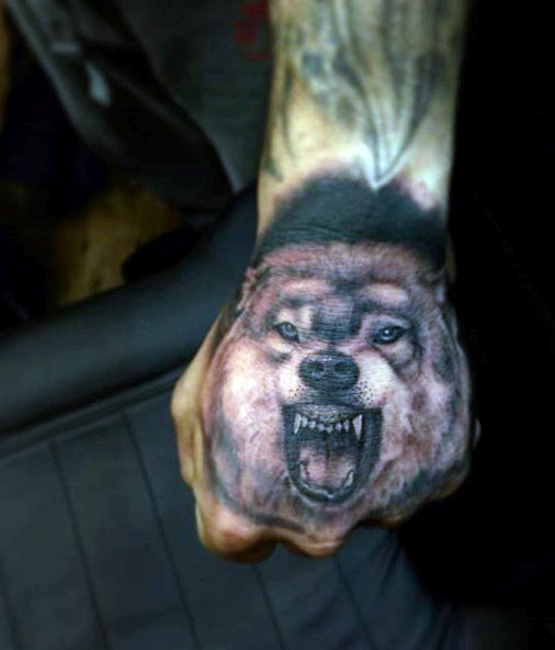 Black and gray style colored hand tattoo of evil wolf