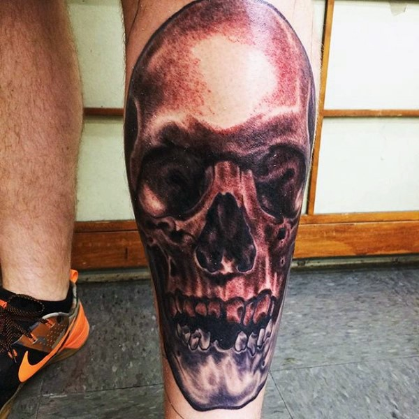 Black and gray style colored leg tattoo of simple human skull