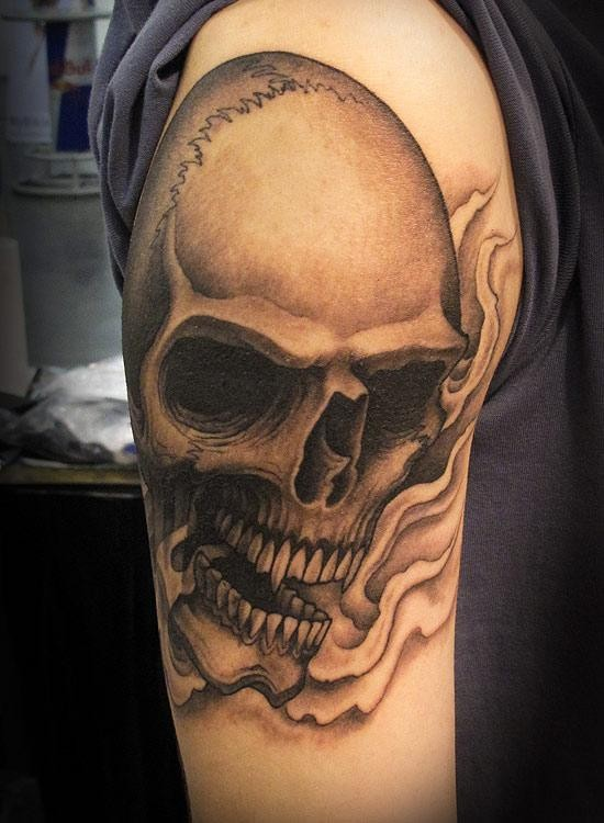 Black and gray style colored shoulder tattoo of human skull