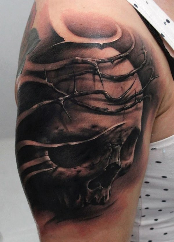 Black and gray style colored shoulder tattoo of human skull with vine