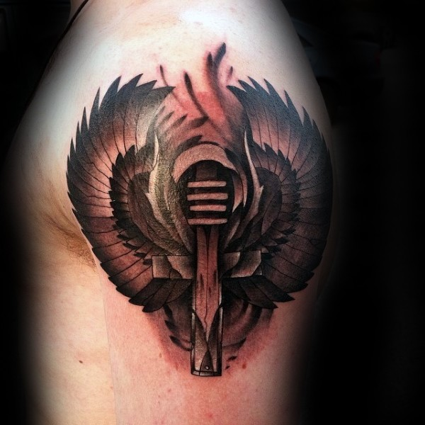 Black and gray style colored shoulder tattoo of cross with big wings