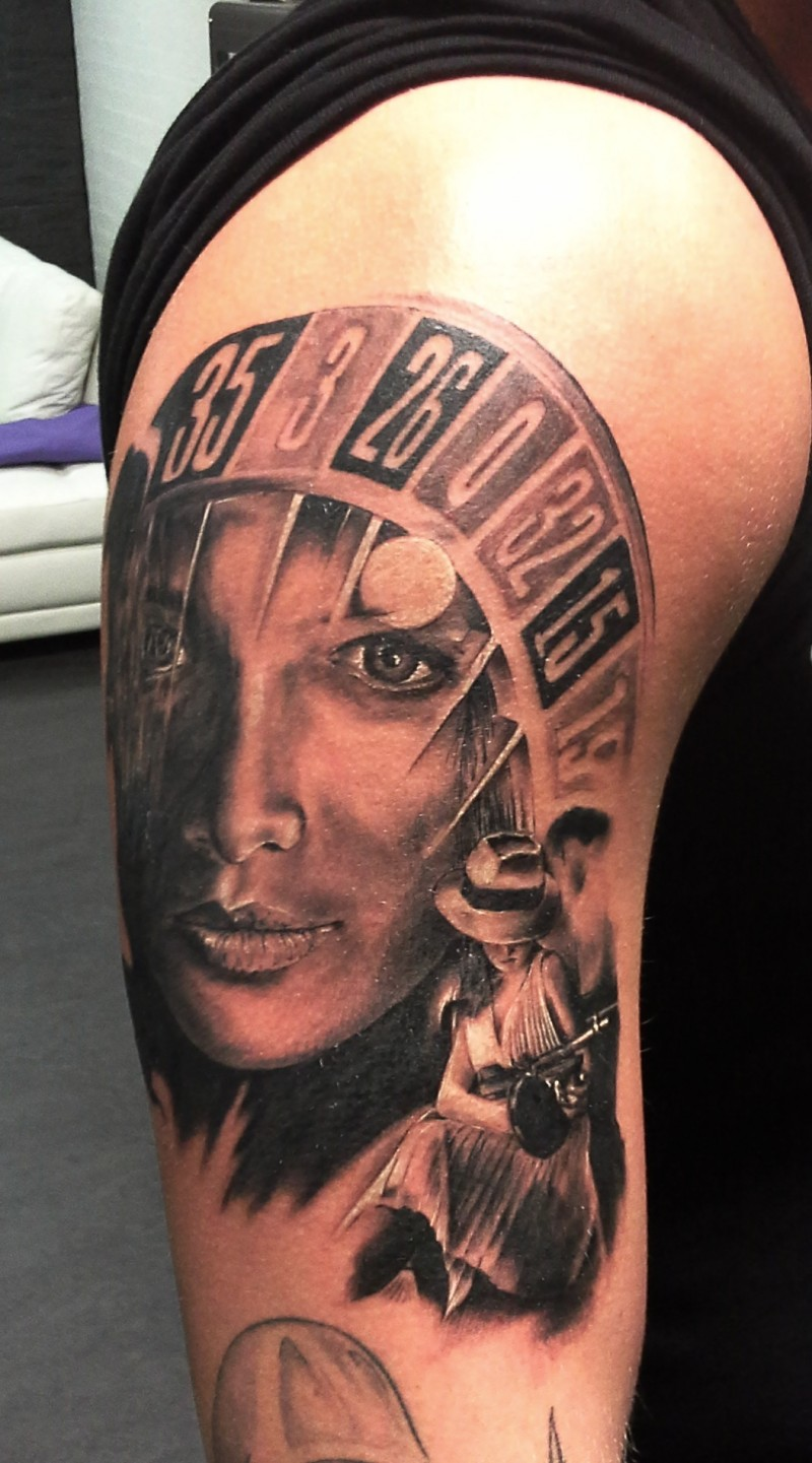 Black and gray style colored shoulder tattoo of roulette with human face