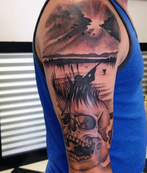 Black and gray style colored shoulder tattoo of hunter with human skull