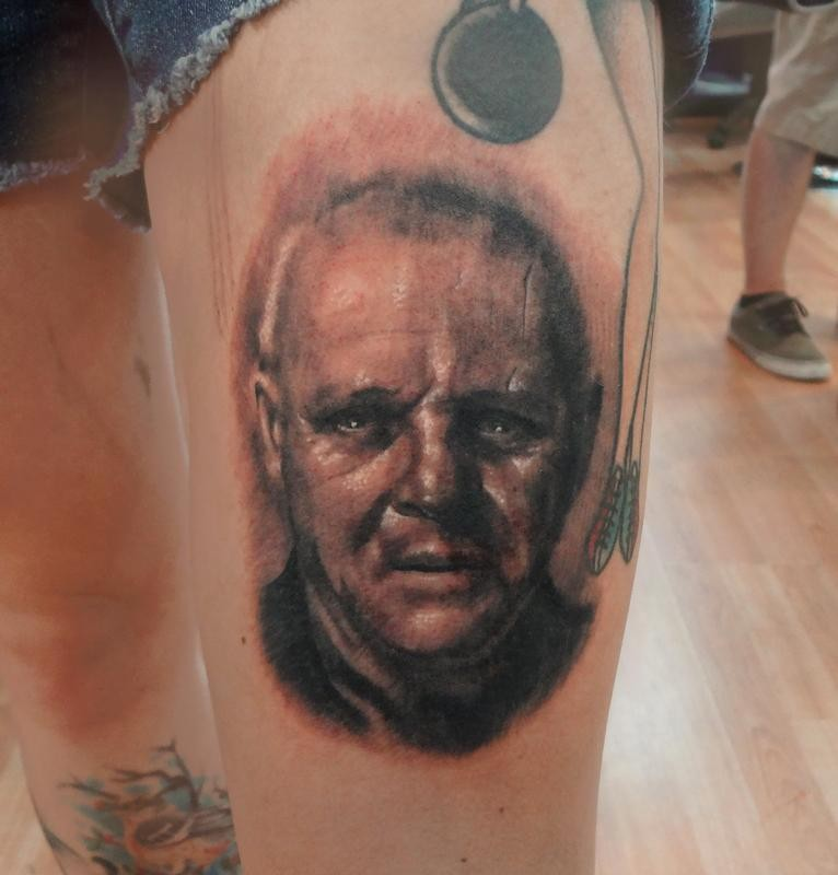 Black and gray style colored thigh tattoo of Hannibal Lector portrait