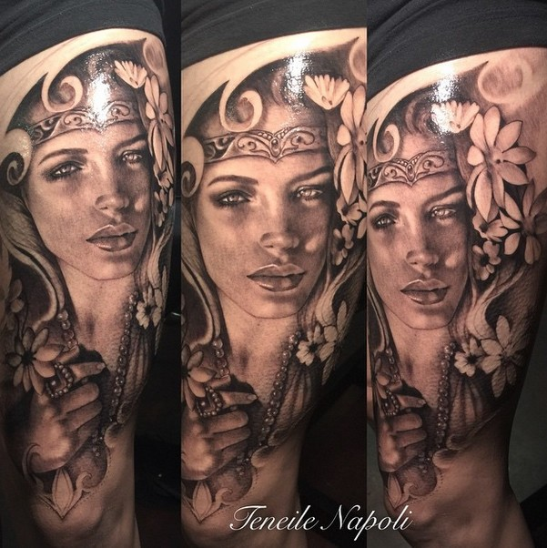 Black and gray style colored thigh tattoo of woman with flowers