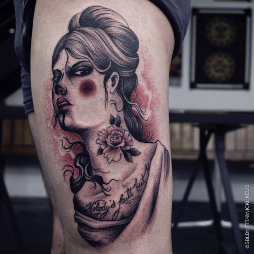 Black and gray style colored thigh tattoo woman face with lettering and flower