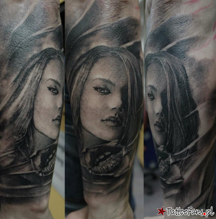 Black and gray style detailed arm tattoo of woman with piercing