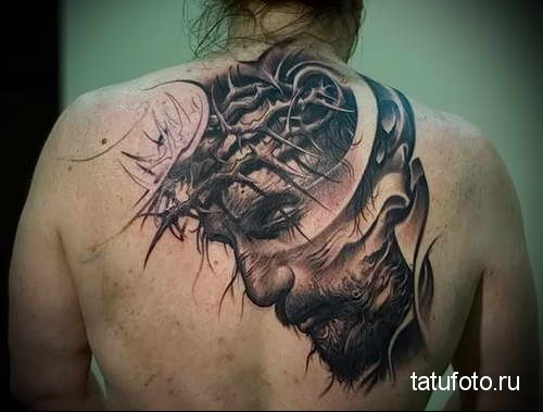 Black and gray style detailed back tattoo of Jesus face with vine