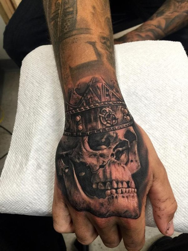 Black and gray style detailed hand tattoo of king skull